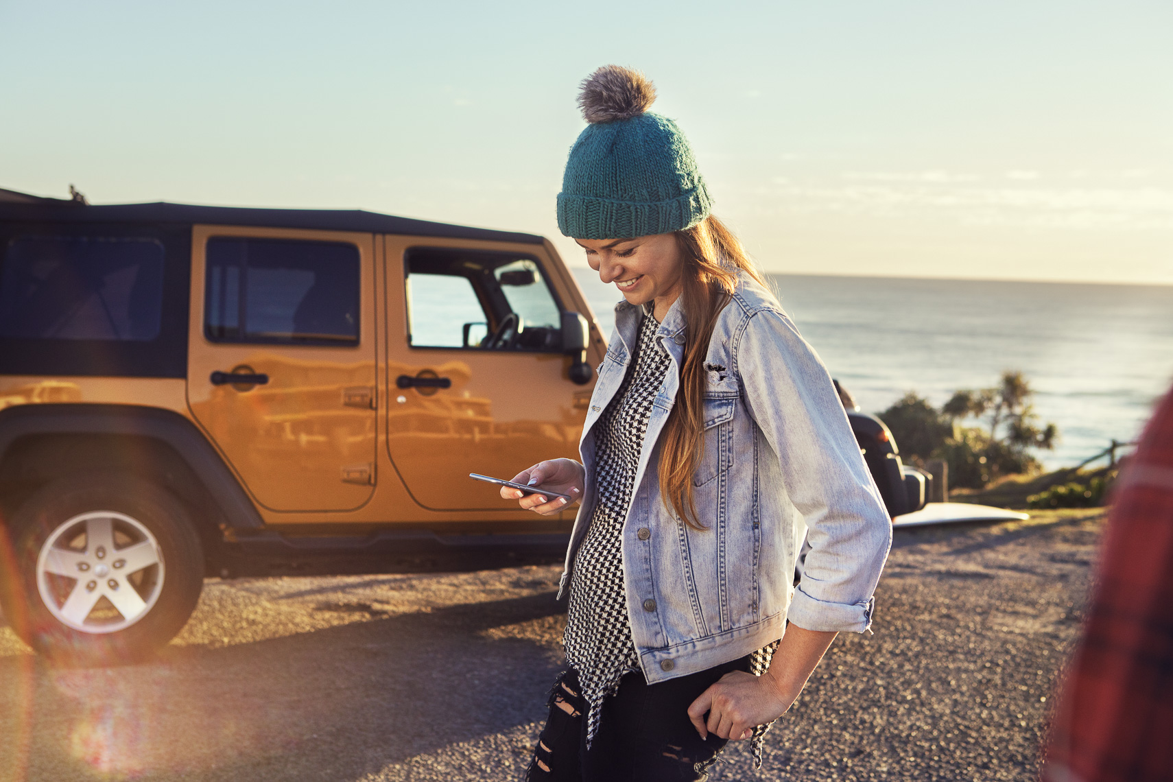 A girl smiling at her phone with an orange jeep in the background