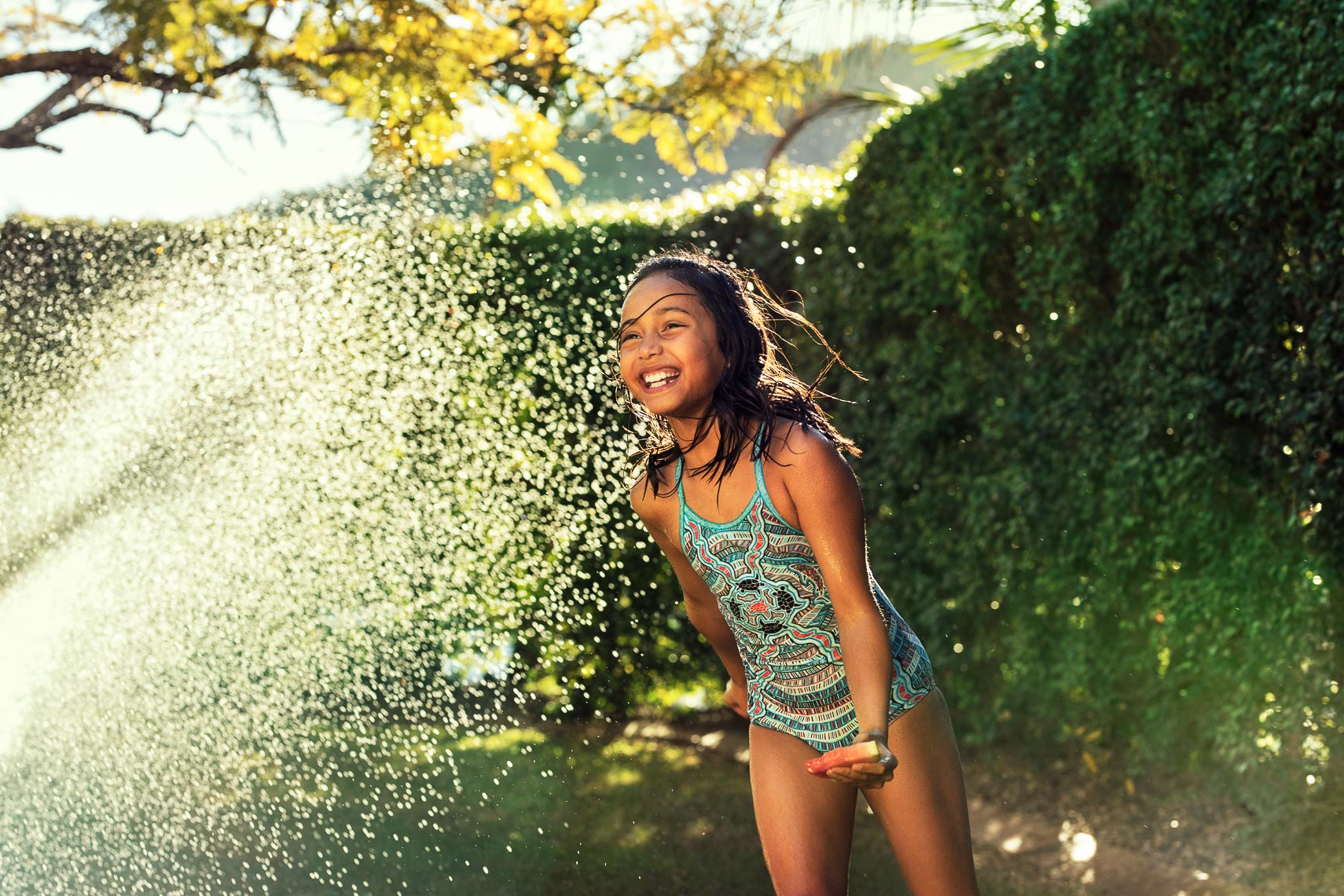 A girl running through water with fruit in her hand for Heritage Bank during an advertising campaign