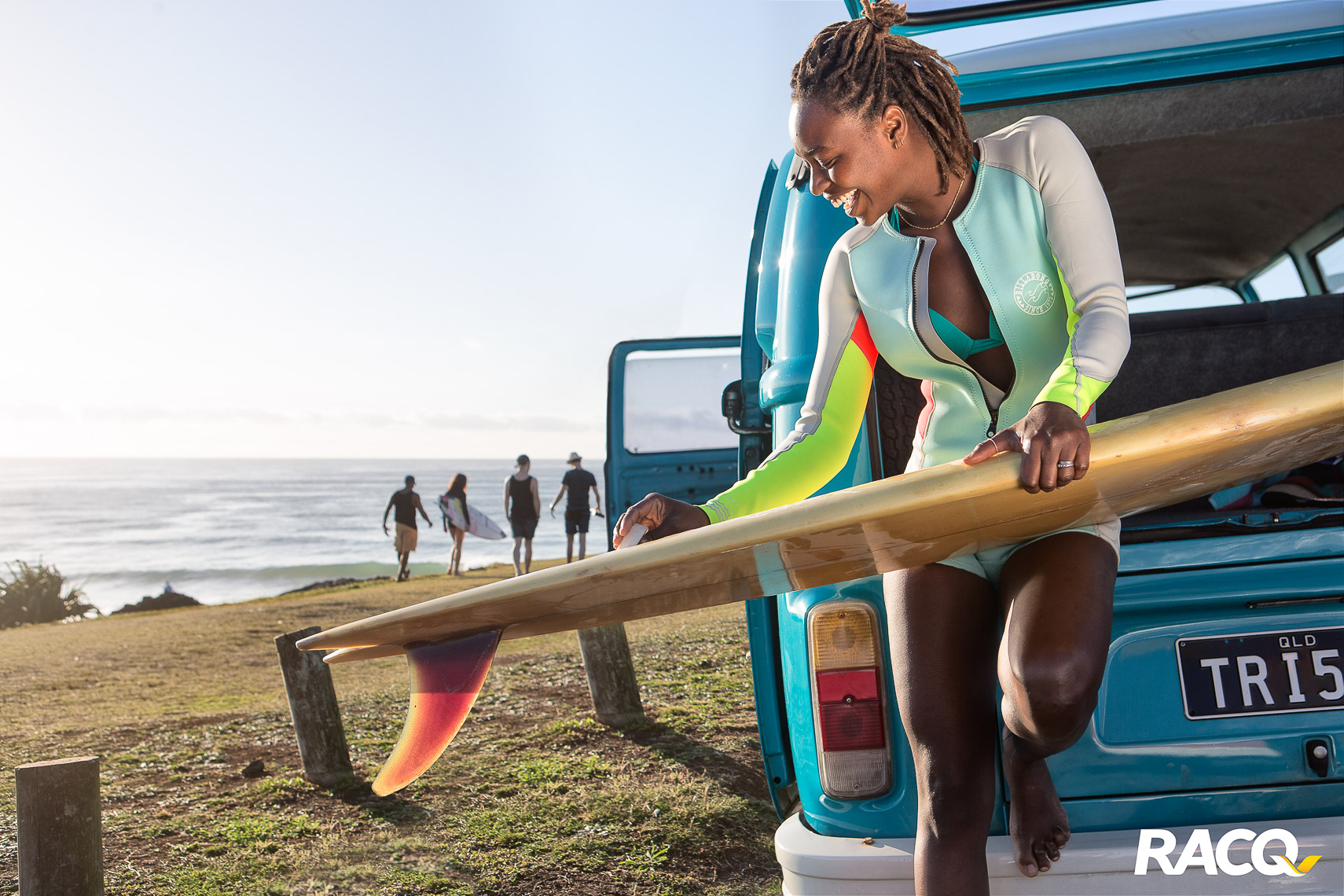 an african girl waxing up her surfboard in Sydney