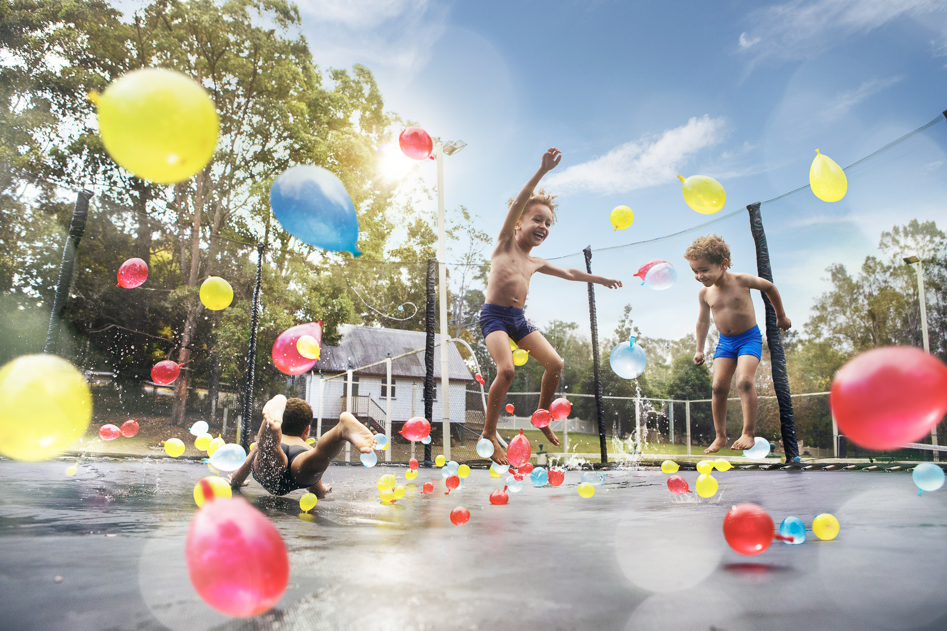 three young boys jumping on a trampoline with water balloons. Photography by Jack Harlem